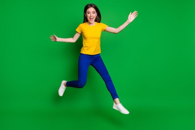Volledige lengte lichaamsgrootte weergave van vrolijk slank meisje springen met plezier