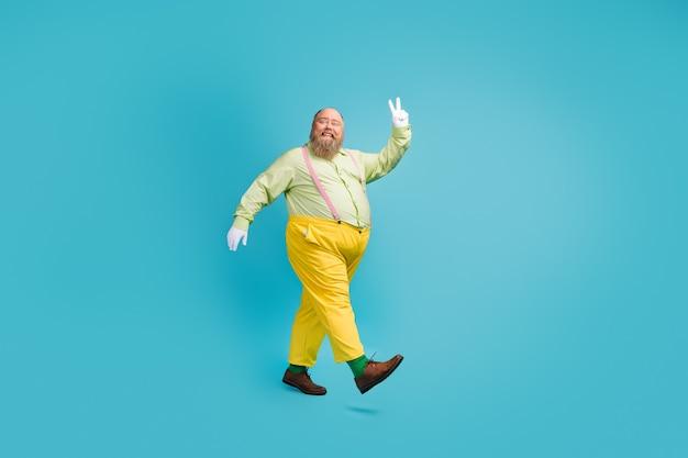 Volledige lengte lichaamsgrootte weergave van vrolijke man lopen met v-teken
