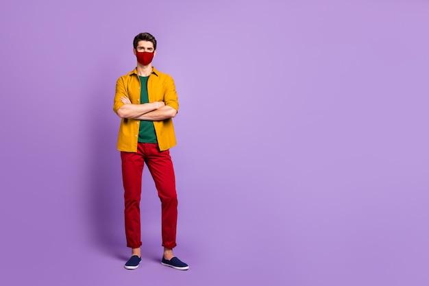 Volledige lengte lichaamsgrootte weergave van zijn hij tevreden man draagt veiligheid rood herbruikbaar veilig masker stop besmettelijke mers cov griep griepgriep besmetting gevouwen arm geïsoleerd violet lila pastel kleur achtergrond