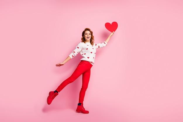 Volledige lengte lichaamsgrootte weergave vrij modieus blij vrolijk meisje stijgende hartdroom in de hand te houden