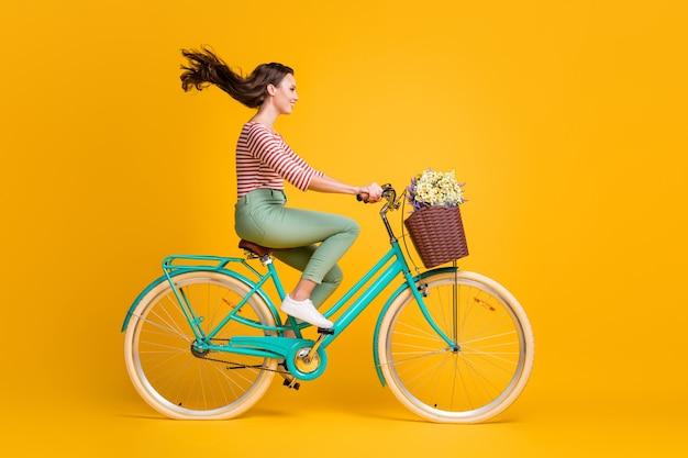 Volledige lengte lichaamsgrootte zijprofiel foto van meisje op blauwe fiets met mand met wilde bloemen geïsoleerd op levendige gele kleur achtergrond