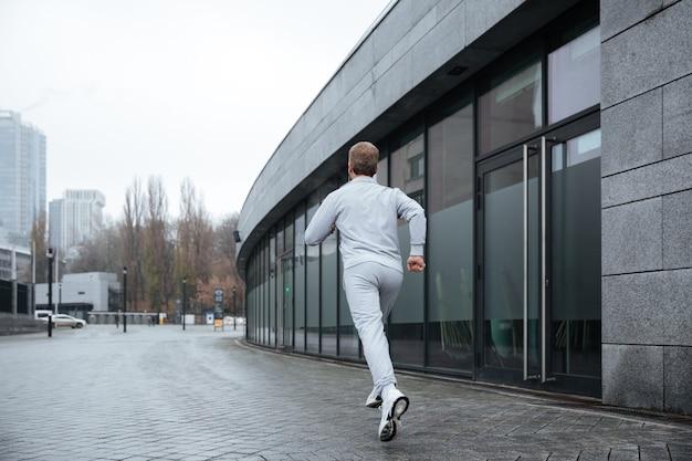 Volledige lengte man in grijze sportkleding die op straat loopt. achteraanzicht