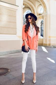 Volledige lengte mode portret van modieuze vrouw in casual outfit wandelen in de stad.