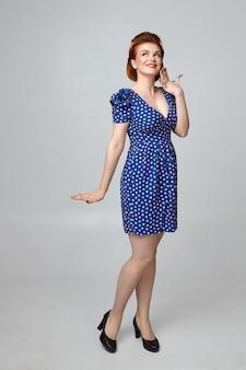 Volledige lengte mooie europese pin-up girl in stijlvolle blauwe jurk met lage hals met verlegen blik, breed glimlachend terwijl flirten met iemand. menselijke gezichtsuitdrukkingen en lichaam