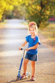 Volledige lengte ortrait van speels leuk glimlachend meisje met autoped in het zachte licht van de avondzon