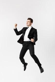 Volledige lengte portret grappige vrolijke zakenman springen in de lucht over grijze achtergrond