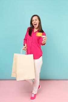 Volledige lengte portret lachende jonge vrouw in roze shirt blouse, witte broek houden boodschappentassen geïsoleerd op fel roze blauwe pastel muur.