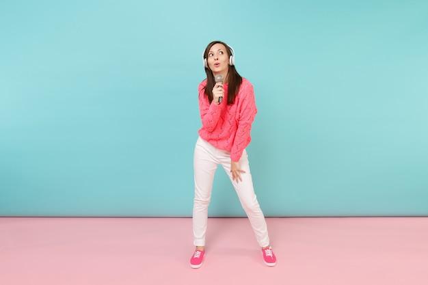 Volledige lengte portret leuke vrouw in gebreide trui, witte broek, koptelefoon zingen lied in microfoon