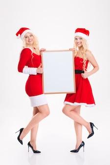 Volledige lengte portret van charmante jonge zusters tweeling in rode kerstman jurken en hoeden met leeg bord op witte achtergrond
