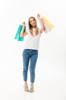 Volledige lengte portret van een mooie jonge vrouw poseren met boodschappentassen, geïsoleerd op een witte achtergrond