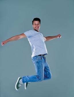 Volledige lengte portret van een opgewonden jonge man in grijs t-shirt springen terwijl het vieren van succes geïsoleerd over grijze achtergrond.