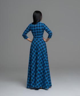 Volledige lengte portret van een sexy brunette vrouw in fashion dress achteraanzicht