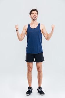 Volledige lengte portret van een vrolijke fitness man geïsoleerd op een grijze achtergrond gray