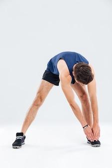 Volledige lengte portret van fitness man die zich uitstrekt en opwarmt op witte achtergrond