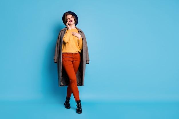 Volledige lengte portret van grappige dame reiziger sprekende telefoon vrienden vertellen adres winkelcentrum slijtage seizoen lange grijze jas trui broek hoed laarzen.