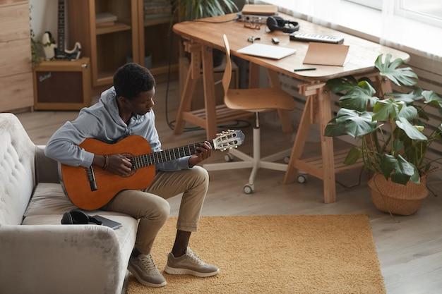 Volledige lengte portret van jonge afro-amerikaanse man akoestische gitaar spelen zittend op de bank thuis, kopieer ruimte