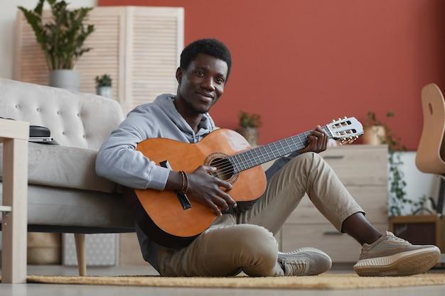 Volledige lengte portret van jonge afro-amerikaanse man gitaarspelen en glimlachen naar de camera zittend op de vloer thuis, kopieer ruimte