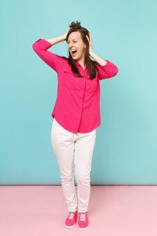 Volledige lengte portret van lachende jonge mooie vrouw in roze shirt blouse, witte broek poseren geïsoleerd op fel roze blauwe pastel muur.