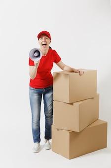 Volledige lengte portret van levering vrouw in rode dop, t-shirt geïsoleerd op een witte achtergrond. vrouwelijke koerier schreeuwen in megafoon in de buurt van lege kartonnen dozen. pakket ontvangen. kopieer ruimte advertentie.