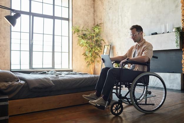Volledige lengte portret van moderne jonge man in rolstoel met behulp van laptop thuis in designer interieur, kopieer ruimte