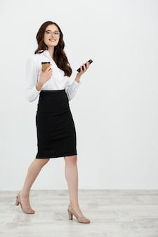 Volledige lengte portret van mooie jonge zakenvrouw in formele slijtage wandelen en sms'en op mobiele telefoon met afhaalmaaltijden koffie in de hand geïsoleerd over grijze achtergrond