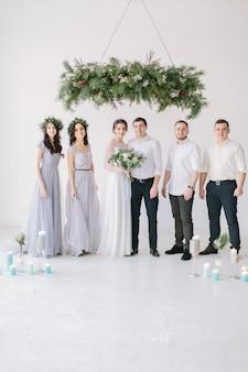 Volledige lengte portret van pasgetrouwde stel en hun vrienden op het huwelijksfeest