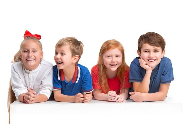 Volledige lengte portret van schattige kleine kinderen meisjes en jongens in stijlvolle kleding camera kijken en lachend tegen witte studio muur. kindermode concept