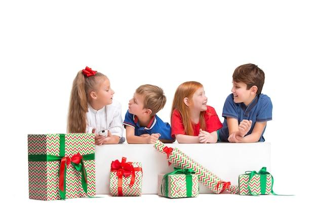 Volledige lengte portret van schattige kleine kinderen meisjes en jongens in stijlvolle kleding camera kijken en lachend tegen witte studio muur met geschenken. kindermode concept
