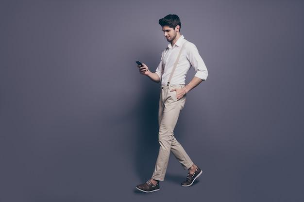 Volledige lengte profiel kant portret van aantrekkelijke luxe man ga copyspace lopen gebruik smartphone chat met blog volgelingen geheime bewonderaars dragen goed uitziende outfit.