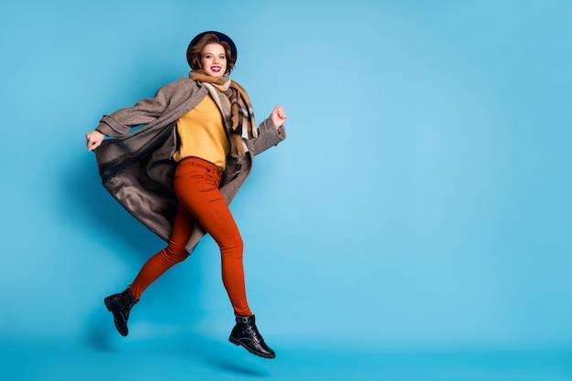 Volledige lengte profiel portret van geweldige dame springen hoog goed humeur haasten snel verslaafde shopper dragen casual lange grijze jas sjaal broek pet schoenen.
