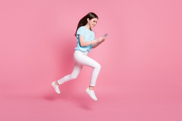 Volledige lengte profiel zijfoto van meisje springen gebruik smartphone rennen draag t-shirt broek geïsoleerde pastel kleur achtergrond