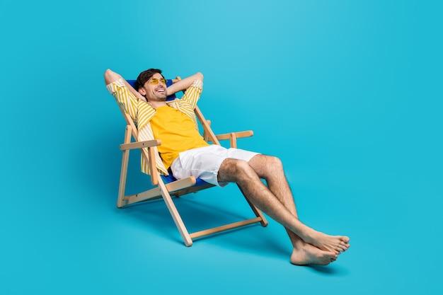 Volledige lengte profiel zijfoto van positieve kerel reiziger ontspannen rust strand zonnebaden liggen comfort ligstoel stretch handen dragen witte korte broek geïsoleerd over blauwe kleur achtergrond