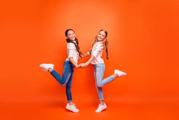 Volledige lengte profiel zijfoto van positieve twee kinderen meisjes rusten herfstvakantie rust ontspannen handen vasthouden draag witte moderne outfit geïsoleerd over oranje kleur achtergrond