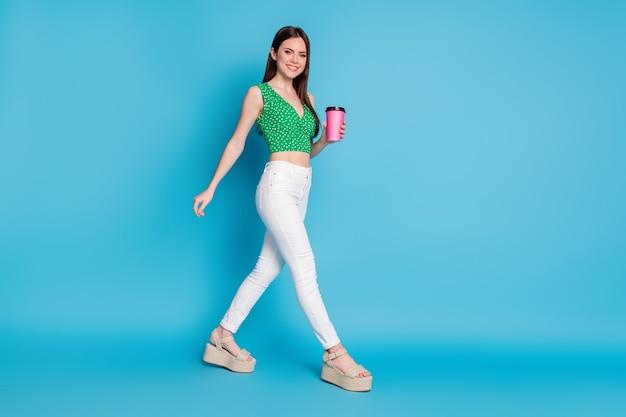 Volledige lengte profiel zijfoto van positieve vrolijke meid houdt koffie meeneembeker vrije tijd lopen copyspace draag singlet sandalen geïsoleerd over blauwe kleur achtergrond