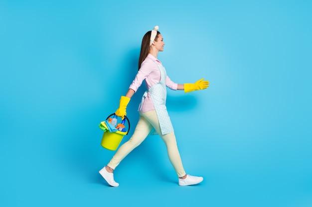 Volledige lengte profiel zijfoto van professionele schoonmaker vrouw go