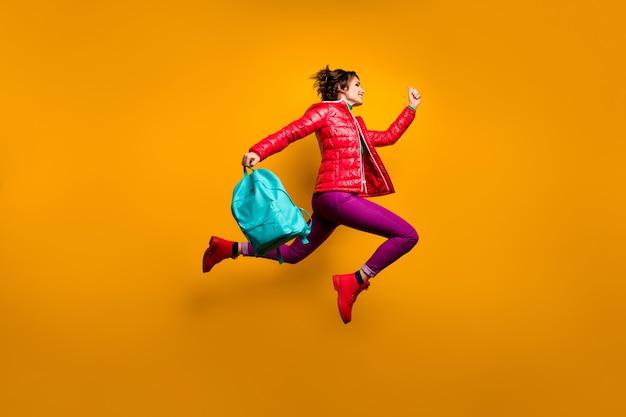 Volledige lengte profiel zijfoto van vrolijke college meisje sprong rennen houden blauwe tas dragen paarse outfit bovenkleding schoeisel stijlvolle trendy heldere glans