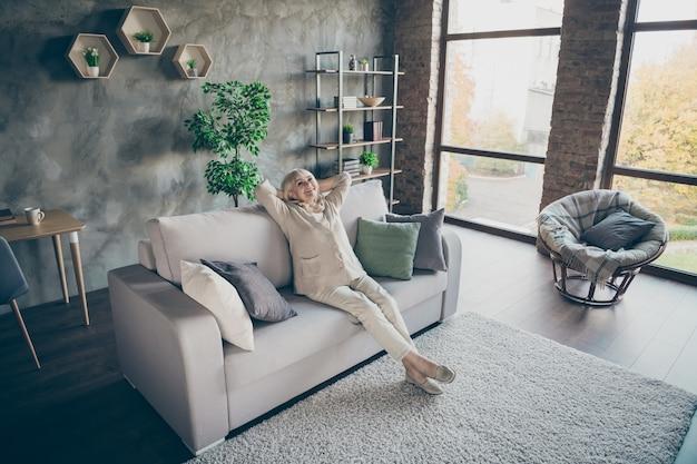 Volledige lengte profielfoto van blonde oude oma goed humeur handen achter het hoofd kijkend plafond genieten van nieuwe huisstijl design zitten comfort sofa divan woonkamer binnenshuis