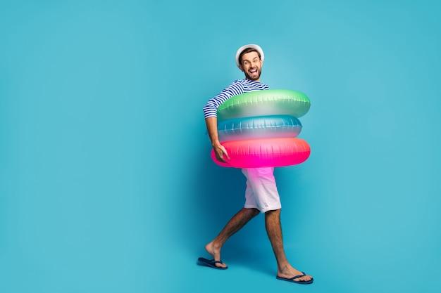 Volledige lengte profielfoto van funky kerel toerist wandelen aan zee binnen drie kleurrijke rubberen reddingsboeien zwemmer dragen gestreepte matroos shirt pet korte broek flip flops geïsoleerde blauwe kleur