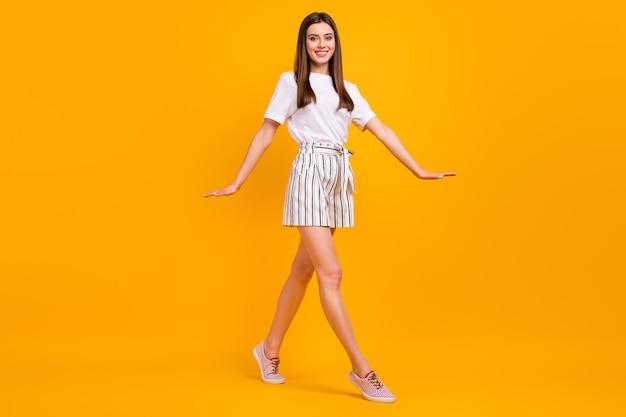 Volledige lengte profielfoto van mooie dame die over straat loopt geniet van zonnige dag weer draag casual wit t-shirt gestreepte mini korte broek schoenen geïsoleerd levendige gele kleur muur