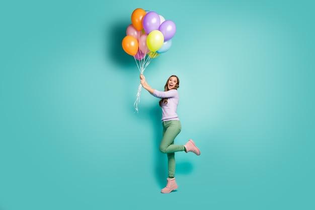 Volledige lengte profielfoto van mooie funky dame houdt veel kleurrijke luchtballonnen vast die wegvliegen met wind waait dragen lila trui groene broek laarzen geïsoleerde groenblauw pastelkleur
