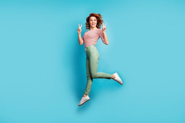 Volledige lengte profielfoto van mooie gekke dame hoog springen met v-teken symbolen verheugend dragen casual rood wit overhemd groene broek sneakers geïsoleerde blauwe kleur