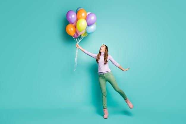Volledige lengte profielfoto van mooie gekke dame houdt veel kleurrijke luchtballonnen wegvliegen met wind waait dragen lila trui groene broek schoenen geïsoleerd groenblauw pastelkleur