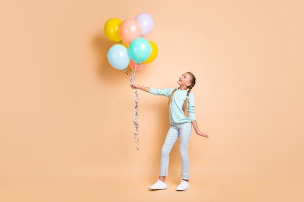Volledige lengte profielfoto van mooie kleine dame houdt veel luchtballonnen dromerig opzoeken lange vlechten dragen blauwe trui jeans sneakers geïsoleerde beige pastelkleur muur