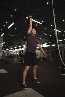 Volledige lengte shot van een gespierde jonge man traint met kettlebell in de sportschool