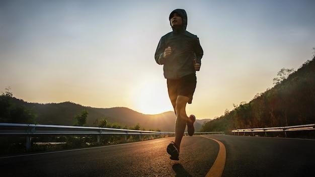 Volledige lengte shot van een gezonde jonge man die 's ochtends op de asfaltweg loopt