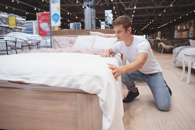 Volledige lengte shot van een man die een nieuw bed kiest om te kopen bij een plaatselijke meubelwinkel