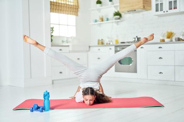 Volledige lengte shot van een mooi spaans tienermeisje met sportkleding die yoga beoefent en thuis oefeningen doet op een mat. training, oefeningsconcept