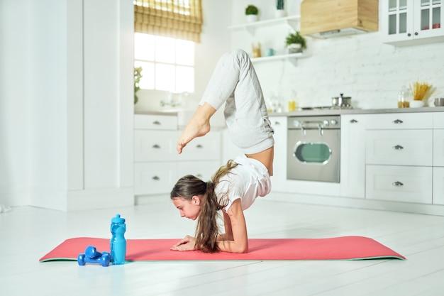 Volledige lengte shot van een mooi spaans tienermeisje met sportkleding die yoga beoefent en thuis oefeningen doet op een mat. training, uitoefening concept. zijaanzicht