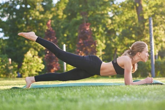 Volledige lengte shot van een mooie fitness vrouw trainen in de ochtend in het plaatselijke park fit afgezwakt spieren kracht evenwicht motivatie.