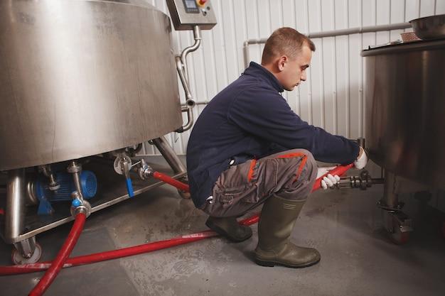 Volledige lengte shot van een werknemer die microbrouwerijapparatuur voorbereidt op het brouwen van bier